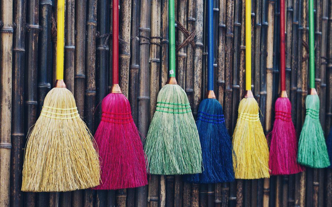 7 bunte Reisigbesen hängen an einer Wand